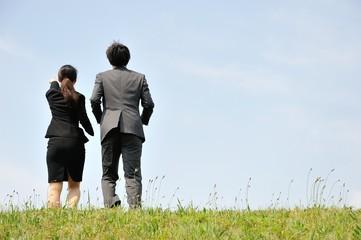 草原を歩くスーツのビジネスマンの男女
