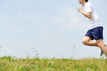 緑の草原の上を走るスポーツウェアの男性