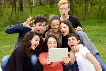 Group of friends having fun while using a tablet in a park