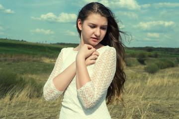 Молодая красивая девушка на фоне неба и полей