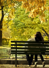 Romantic couple sitting in the autumn park