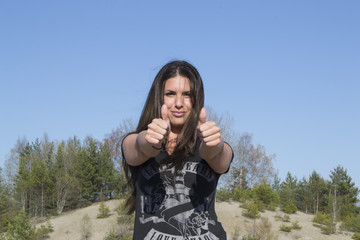 Pretty woman showing thumbs-up in the air (success)