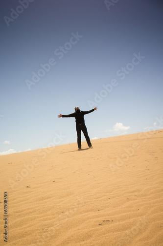 jubelnder Mann auf einsamer Sanddüne