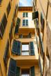 Facciata palazzo giallo con finestre e persiane - 64509549