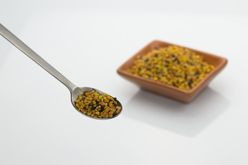 bee pollen grains with spoon on white background