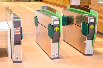 Turnstiles in underground railway station. Green arrows pointing