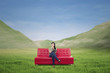 Attractive woman having coffee on red sofa outdoor
