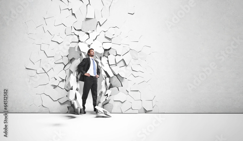 businessman breaking trough a wall