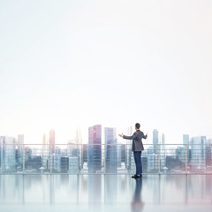 Business man standing on a roof and looking at city