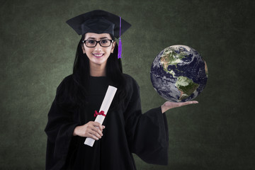 Beautiful female graduate holding earth in class