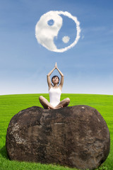 Beautiful woman doing yoga meditation under ying yang cloud