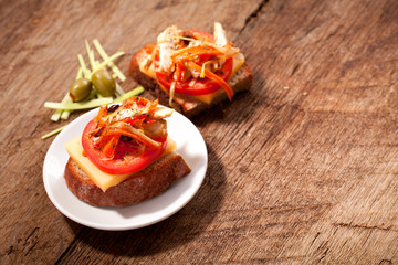 Sandwich with tomato on a table with meat, tomato and olives