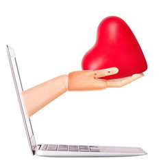 wooden hand with a heart - gift and laptop