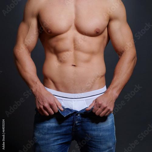 canvas print picture Mann mit musulösen Körper öffnet seine Hose