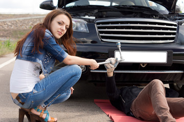 Attractive trendy young woman fixing her car