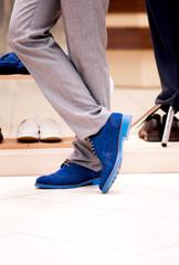 Man chooses a shoes  at a shop.