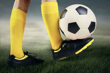 Foot controlling soccer ball at field