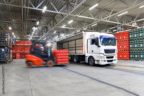 Leinwanddruck Bild beladen von LKW in Logistikhalle // shipping