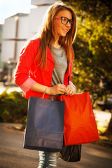 Teenage girl walking on the street with shopping bags