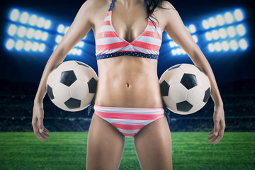 Sexy woman holding soccer balls at field