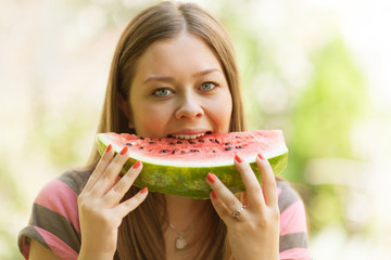 Beautiful girl eating watermelon sitting on the grass.