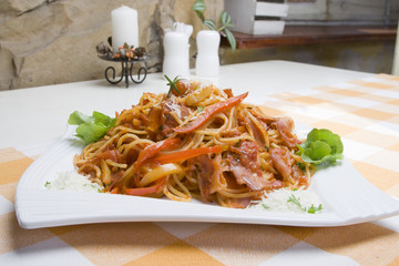 Spaghetti with bacon on the table.