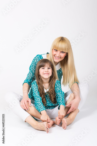 Mother and daughter hug sitting wearing matching outfit
