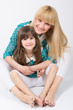 Mother and daughter with long hair with bangs smiling