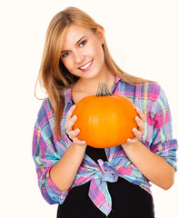 beautiful young woman holding pumpkin and smiling