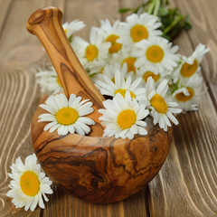 Wooden mortar and daisies