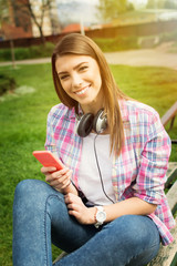 Beautiful young woman with phone and headphones in park