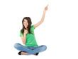 Lachende junge Frau im Schneidersitz isoliert präsentiert
