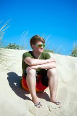 Teenager sitzt auf Sanddüne