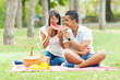 Portrait of a young couple eating watermelon at a picnic