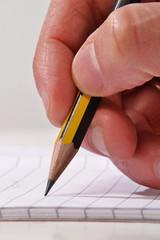 Mano escribiendo con un lápiz en un cuaderno.