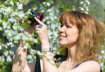 Young woman photographs cherry blossom