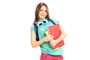 Smiling female with schoolbag and headphones leaning on a wall