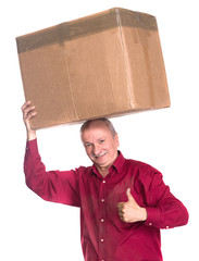 Senior man carries a heavy box