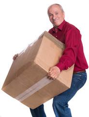 Senior man carries a heavy box