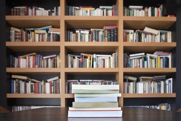 Pila de libros con librería de fondo