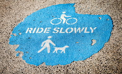 "Weathered Sign on Pavement Saying ""Ride Slowly"""