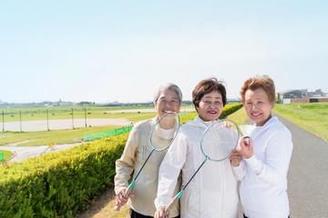 高齢の女性3人がラケットを持って立っている様子