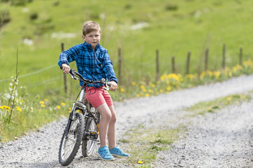 Boy sitting on his bike on a country road