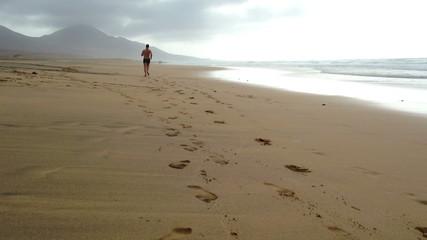 Man jogging on the Cofete beach, Fuerteventura - back view