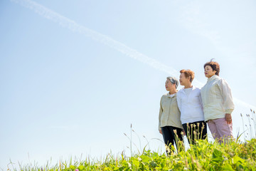 草原の丘の上に立って空を見上げる高齢の3人の日本人女性