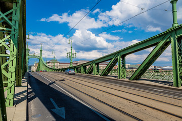 The green Freedom Bridge, with yellow tram, in Budapest,the capi