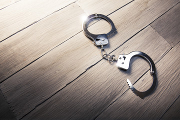 Open Handcuffs on a wooden background
