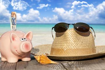 Sparschwein, Strohhut und Sonnenbrille auf dem Holzsteg