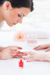 Making red manicure.