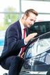 Verkäufer mit Auto im Autohaus